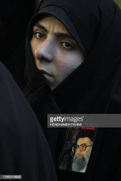 Woman with a portrait of Iranian supreme leader Ayatollah Ali Khamenei pinned to her headscarf attends a ceremony marking the 12th anniversary of the...