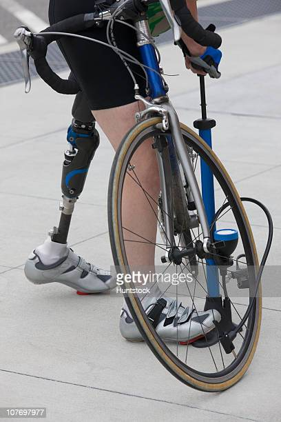 woman with a prosthetic leg pumping air into a bicycle - air pump stock photos and pictures