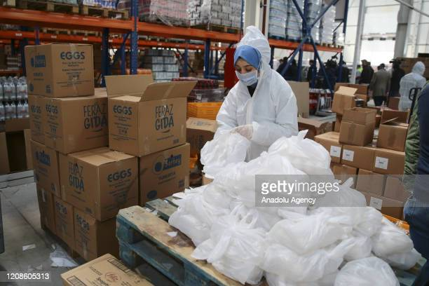 Woman with a protective mask packs 333,000 boxes of relief packages which was prepared with the support of benevolent, to distribution for 50,000...