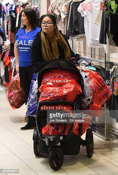 A woman with a pushchair full of shopping leaves the Next department store during the Boxing Day sales at Highcross Shopping Centre in Leicester