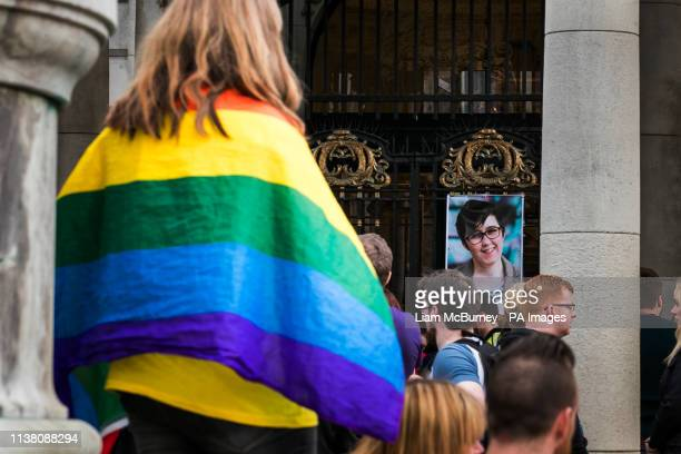 A woman with a rainbow flag at a vigil at Belfast City Hall in memory of murdered journalist Lyra McKee