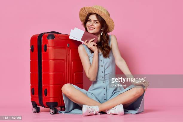 woman with a red suitcase and tickets in hand in the studio on a pink background - red hat stock pictures, royalty-free photos & images