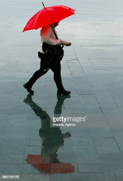 A woman with a red umbrella walks over a wet floor after heavy rainfalls hit Izmir Turkey on November 27 2017 People try to prevent getting caught in...