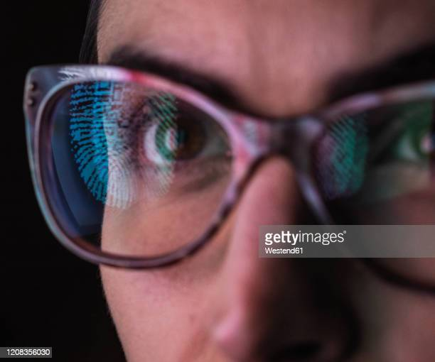 woman with a reflection of a finger print on her glasses to represent identity and access - security stock pictures, royalty-free photos & images
