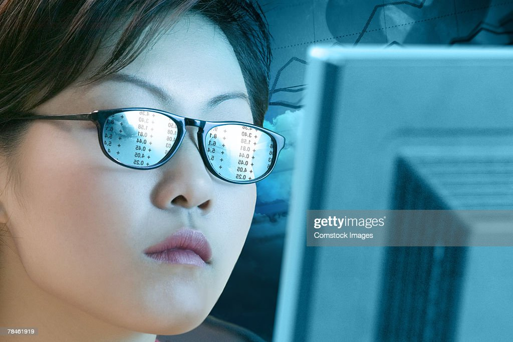 Woman with a reflection off a computer in her glasses : Stock Photo