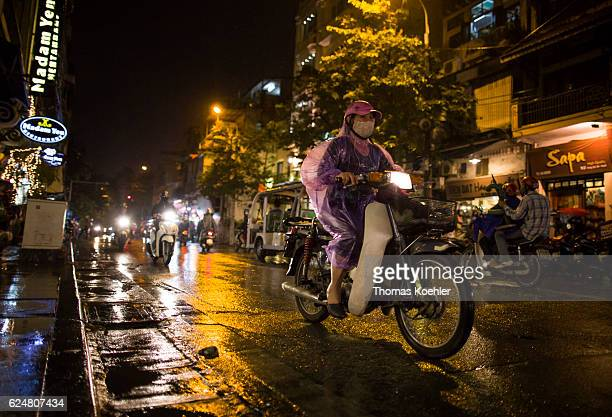 A woman with a respiratory mask is driving on a motorbike in the evening traffic of Hanoi on October 30 2016 in Hanoi Vietnam