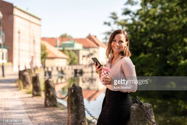 woman with a reusable coffee cup is using her smart phone - medium shot stock pictures, royalty-free photos & images