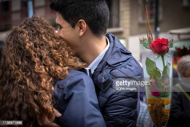 Woman with a rose flower seen embracing her partner during the Sant Jordi day celebration. The festivity of Sant Jordi is celebrated in conjunction...