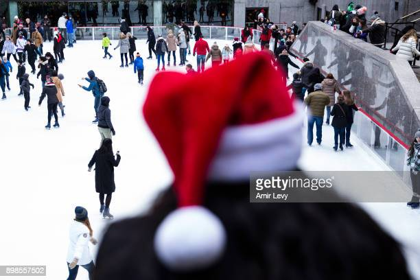 A woman with a Santa hat watches people skate at the ice skating rink at Rockefeller Center on Christmas day on December 25 2017 in New York City...