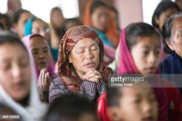 A woman with a sari is praying with closed eyes while a ceremony inside a church in Kalimpong