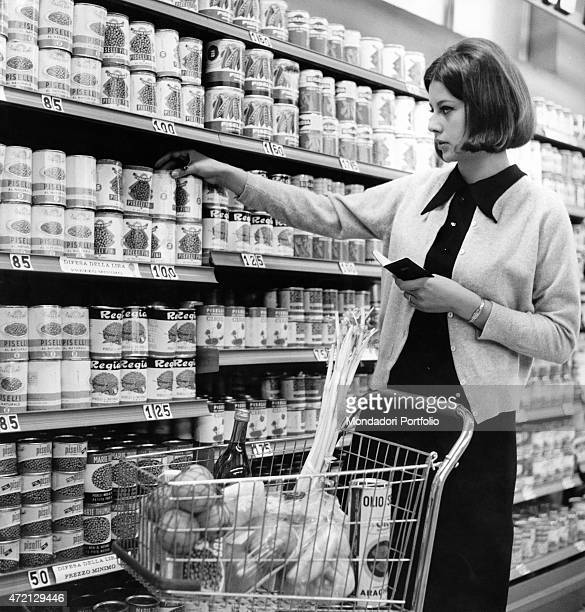 'A woman with a shopping cart buying a can of peas at the supermarket Italy 1964 '