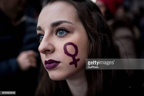 A Woman with a sign depicting the Venus symbol in her cheek takes part in a march organised by 'Non Una Di Meno' movement on March 8 2018 as part of...