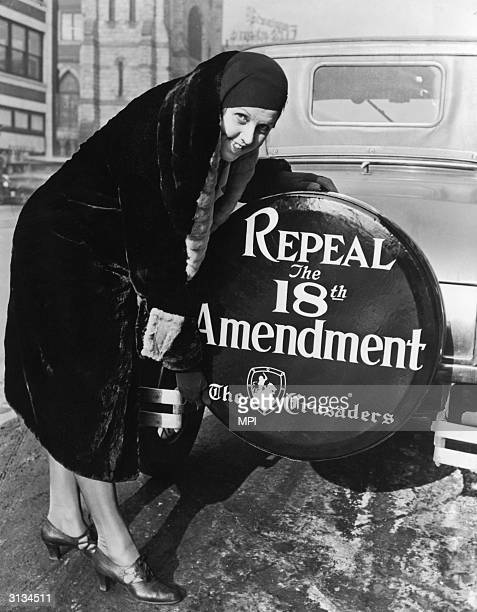 A woman with a sign on the back wheel of her car supporting the repeal of the 18th Amendment which made the sale and possession of alcohol illegal