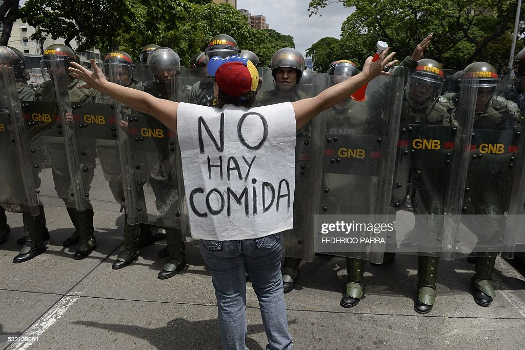 TOPSHOT - A woman with a sign reading 'There is no food' protests against new emergency powers decreed this week by President Nicolas Maduro in front of a line of policemen in Caracas on May 18, 2016. Public outrage was expected to spill onto the streets of Venezuela Wednesday, with planned nationwide protests marking a new low point in Maduro's unpopular rule. / AFP / FEDERICO