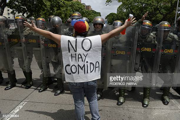 TOPSHOT A woman with a sign reading There is no food protests against new emergency powers decreed this week by President Nicolas Maduro in front of...
