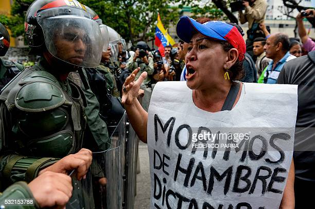 TOPSHOT A woman with a sign reading 'We starve' protests against new emergency powers decreed this week by President Nicolas Maduro in front of a...