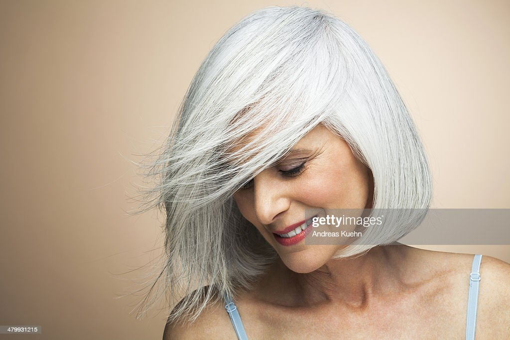 Woman with a silvery,grey bob looking down. : Stock Photo