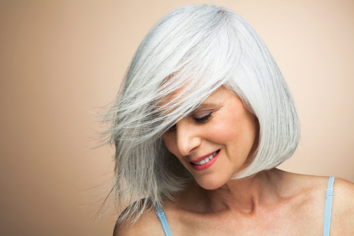 Woman with a silvery,grey bob looking down. - gettyimageskorea