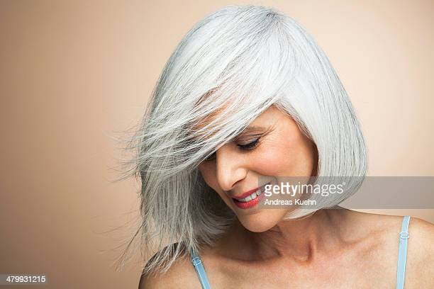 woman with a silvery,grey bob looking down. - graues haar stock-fotos und bilder