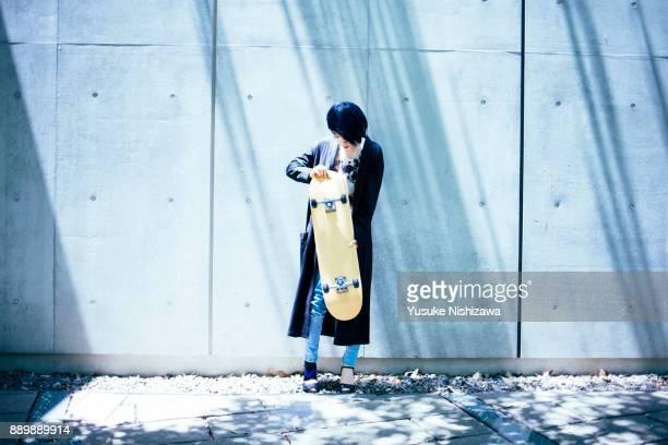 a woman with a skateboard - yusuke nishizawa stock-fotos und bilder