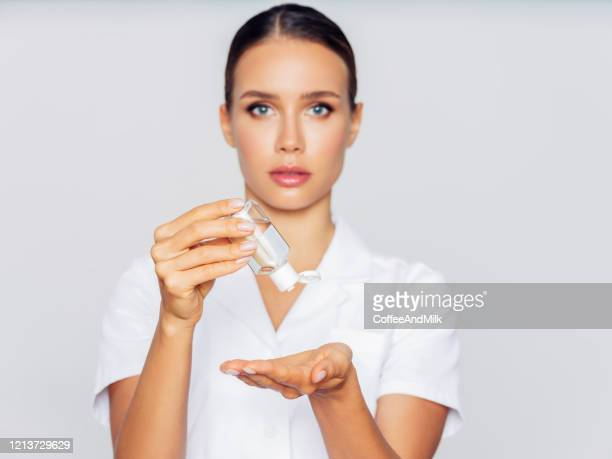 woman with a small bottle of hand sanitizer - antiseptic stock pictures, royalty-free photos & images