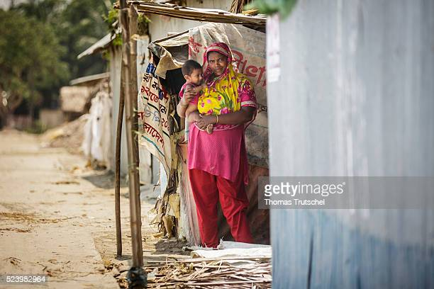 A woman with a small child on her arms standing at the entrance of her hut on April 11 2016 in Khulna Bangladesh