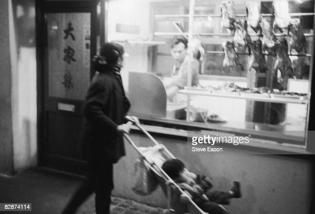 Woman with a small child passes a restaurant in London's Chinatown, 21st October 1992.