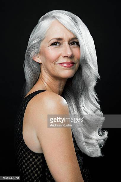 Woman with a soft smile and long, gray hair.