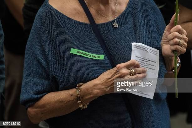 A woman with a sticker which reads 'Democracia on ets' holds a ballot paper during a tribute outside a school which acted as polling station in the...
