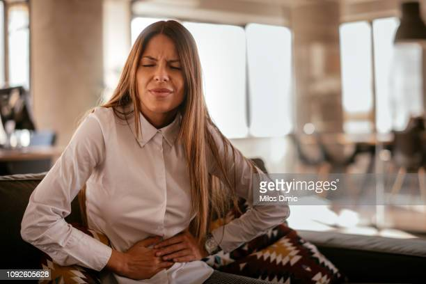 woman with a stomach ache - pain stock pictures, royalty-free photos & images