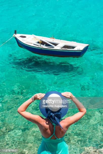 Woman with a straw hat admiring a little boat on the crystal water, Limeni, Mani region, Peloponnese, Greece, Europe