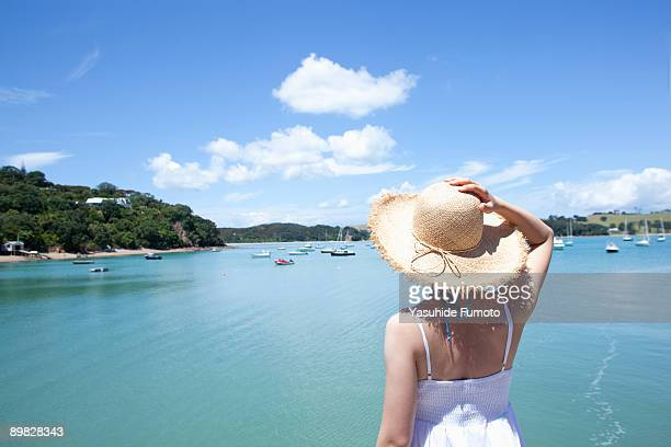A woman with a straw hat looking at the sea.
