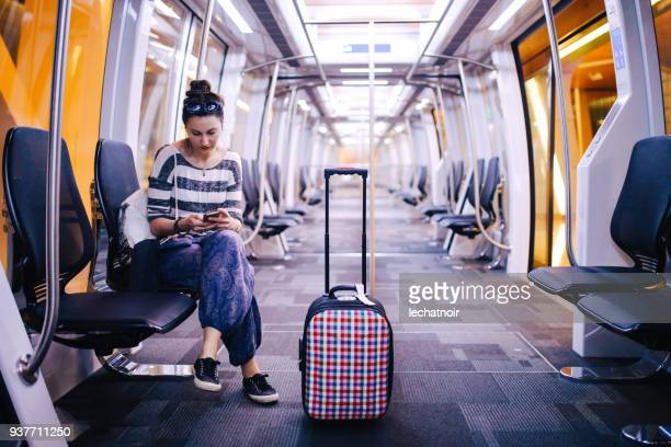 woman with a suitcase traveling solo on the qatar airport shuttle bus - women wearing nothing stock photos and pictures
