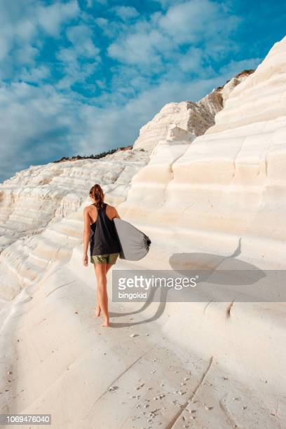 woman with a surfboard on white cliffs - agrigento stock pictures, royalty-free photos & images