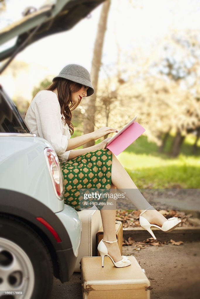 Woman with a tablet sits in the back of a car : Stock Photo