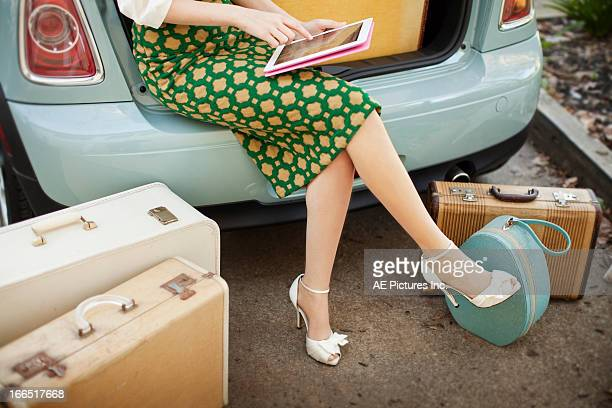 Woman with a tablet sitting in the back of a car