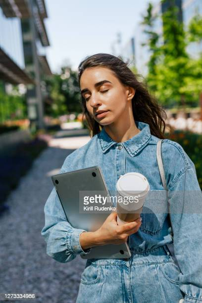 woman with a takeaway coffee and a laptop standing outside - einzelne frau über 30 stock-fotos und bilder