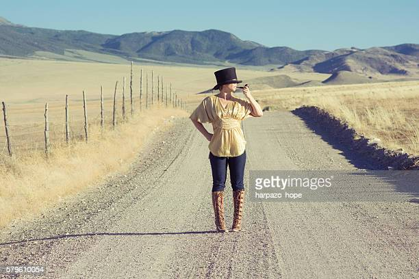 Woman with a top hat standing in the road smoking a tobacco pipe.