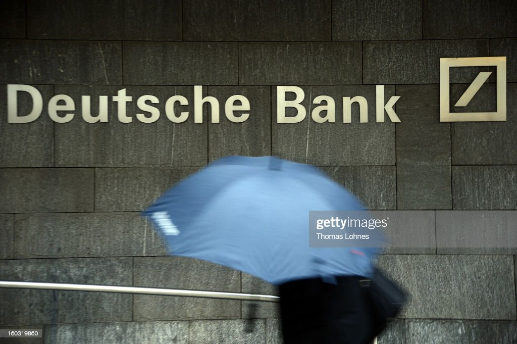 A woman with a umbrella passes a logo of Deutsche Bank on January 29, 2013 in Frankfurt am Main, Germany. The annual results press conference for 2012 takes place on Thursday, January 31, 2013.