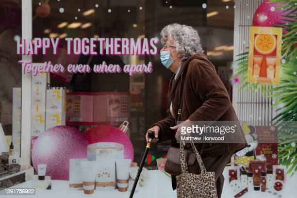 """Woman with a walking stick and surgical face mask walks past a shop with the message """"happy togethermas"""" on November 12, 2020 in Cardiff, Wales."""