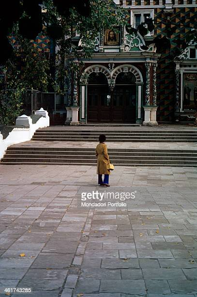 A woman with a yellow raincoat and a handbag stands next to the entrance of the church of Saint Sergius at the Trinity Lavra of Zadorsk the christian...