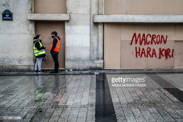 A woman with a yellow vest speaks with a man with a red vest next to a graffiti reading 'Macron Hara Kiri' written on a wooden plank which protects a...