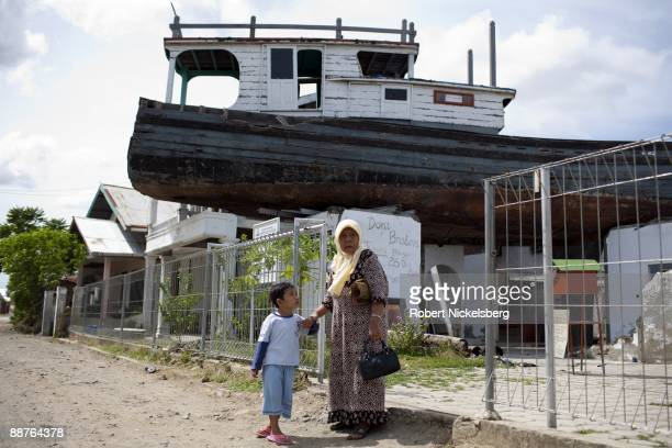 A woman with a young boy walk down a Banda Aceh street where a fishing boat remains on the second story of a house following the December 26 2004...