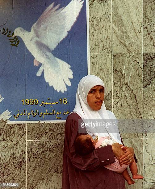 A woman with ababy in her arms stands in front of an electoral poster calling for the referendum of the civil reconciliation 13 September 1999...