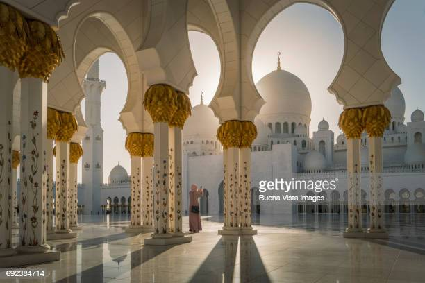woman with abaya taking pictures in a mosque - アブダビ ストックフォトと画像