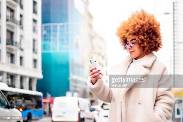 woman with afro blond hair using smart phone while standing on street - kroeshaar stockfoto's en -beelden