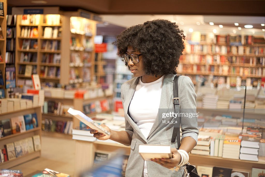 Woman with afro hair choosing books in a bookstore : Stock Photo