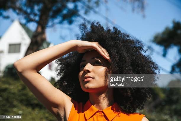 femme avec le cheveu afro couvrant ses yeux du soleil - lumière vive photos et images de collection