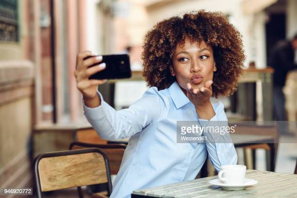 Woman with afro hairstyle sitting in outdoor cafe taking a selfie