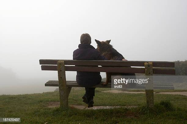 Woman with alsatian dog in mist